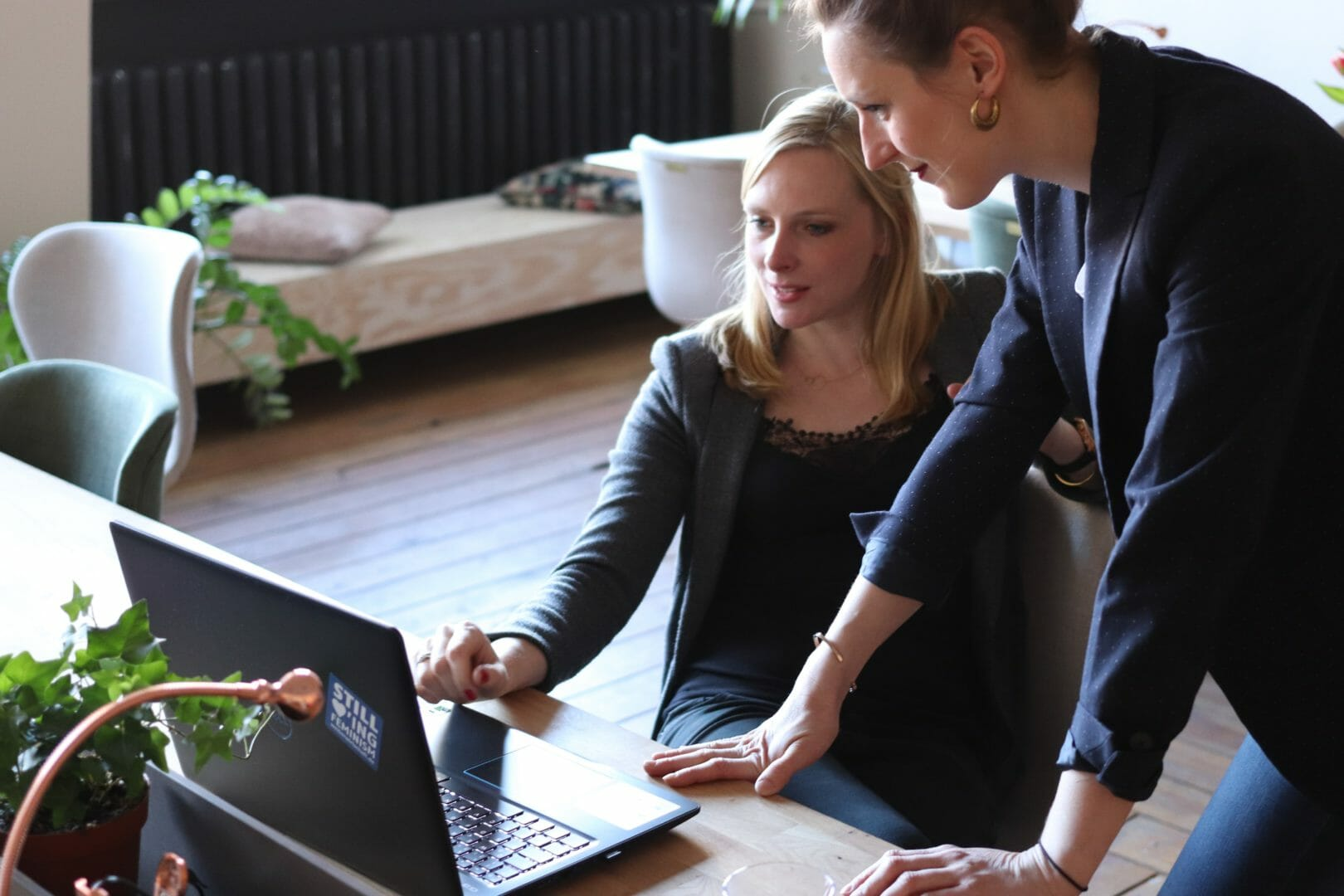 two Women dressed formally looking at laptop